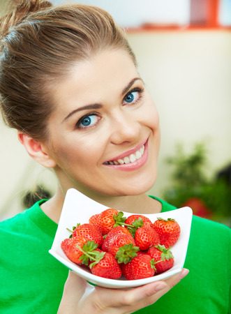 Smiling woman eating strawberry. Close up female face  portrait. Healthy mel on a plate.