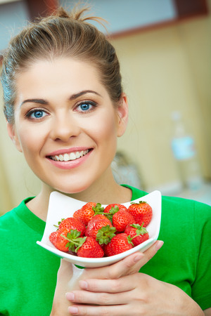 Smiling woman eating strawberry. Close up female face portrait. Healthy mel on a plate Banco de Imagens
