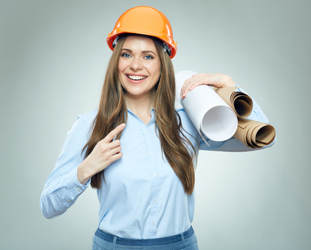 Smiling woman builder with paper plan. Architect student pointing finger.