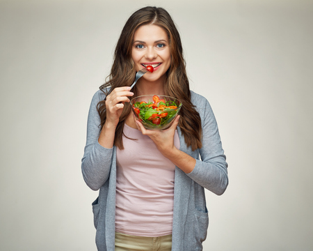 happy woman eating salad from glass bowl with fork. isolated portrait of young woman with healthy food.