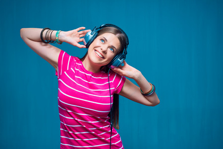 Young woman listening music with earphones on blue background. Stok Fotoğraf