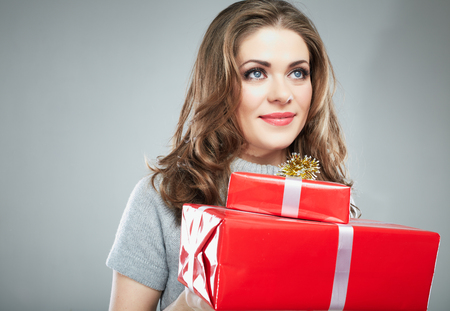 Gift box woman hold against gray background. Close up Isolated portrait of young smiling model.