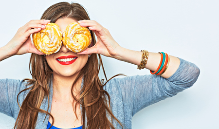 Woman smile with teeth. Two cake. Diet concept. Lon hair model. Imagens