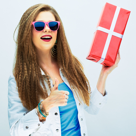 thumb up. happy smiling woman hold red gift  . white studio background .