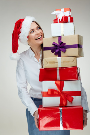 Santa businesswoman holding pile of christmas gifts. Isolated portrait.