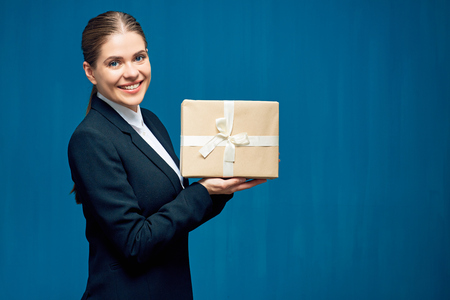 Smiling business woman wearing black suit holding gift box. Portrait on blue.