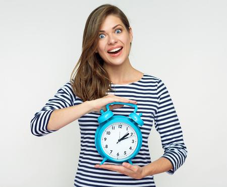 Woman holding big alarm clock. Isolated studio portrait.