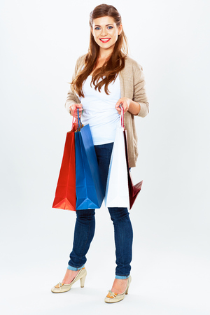 Fashion model with shopping bags. Isolated white background full length portrait. Young woman smile. Stock Photo