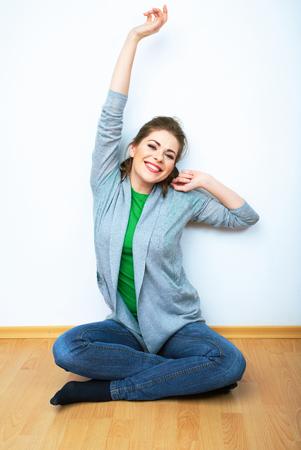 Kobieta naturalny portret siedzenia na podłodze. Białe tło na białym tle. Uśmiechająca się dziewczyna. Zdjęcie Seryjne