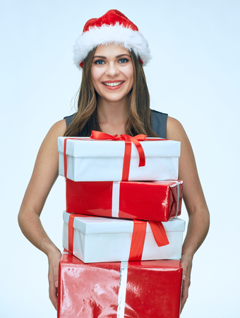 Smiling girl wearing christmas hat hold gift box. Business dress. Isolated portrait.