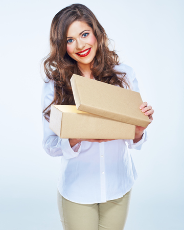 Smiling young woman holding open paper gift box. Model with long curly hair. White business shirt.