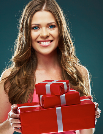 Toothy Smiling happy woman holding red gift box. Studio portrait gray isolated. Young female model. Stock Photo