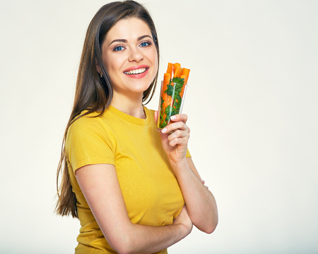 Smiling woman holding glass with carrot stick. Big smile with teeth.
