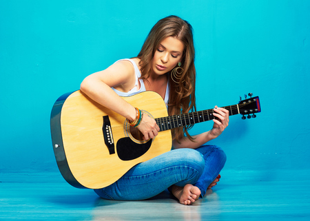 teenager girl singer with guitar sitting on a floor . Standard-Bild