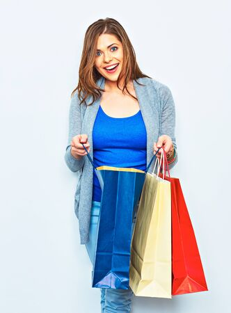 Shopping woman toothy smiling holding bags. one girl studio portrait. beautiful emotional female model.