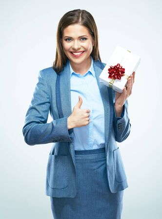Business woman hold gift. Thumb up show. White background isolated portrait. Stock Photo