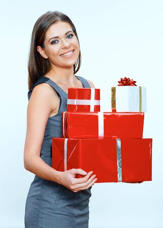 Smiling business woman hold pile of gifts. Red gift box. Studio isolated portrait. Stock Photo