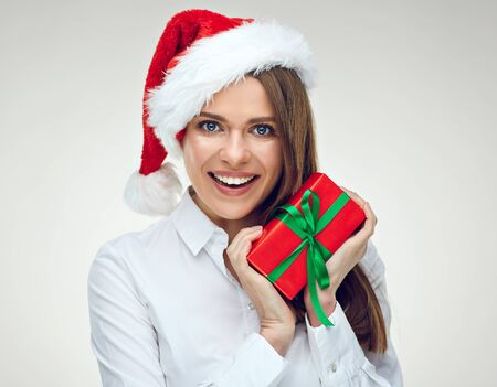 Businesswoman wearing Santa hat holding red gift box. Isolated portrait. Stock Photo