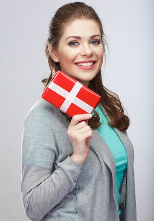 Portrait of young happy smiling woman hold gift box.Smiling girl. Isolated studio background female model. Stock Photo