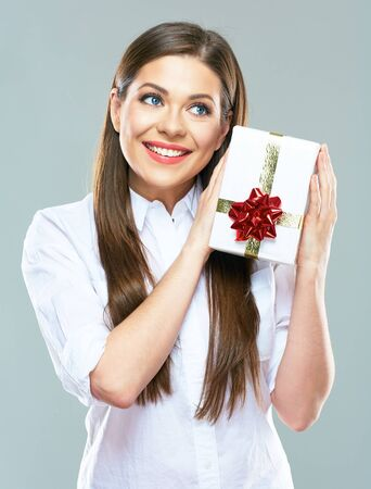 Smiling business woman  holding gift box. Young model studio posing. Present. Stock Photo