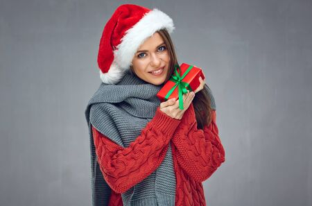Happy woman with toothy smile wearing Christmas hat and holding red gift box with green ribbon. Gray wall back. Stockfoto