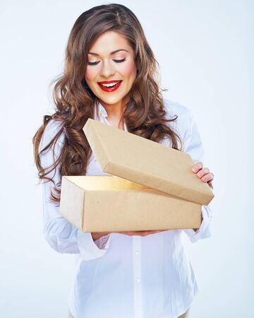 young woman looking into open box. Long curly hair. Beautiful female model. Stock Photo