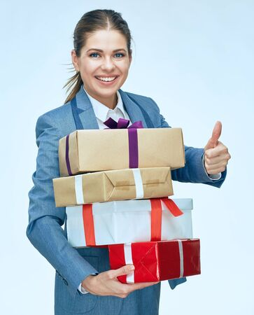 Smiling woman holding gift box showing thumb up. Isolated portrait.