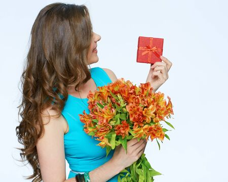Beautiful girl holding flawors bouquet with gift box. Isolated white background. Long hair. Smiling woman.