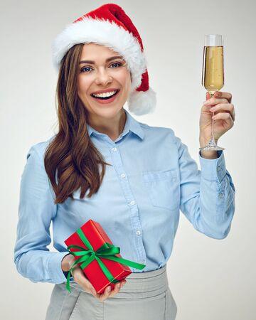 Businesswoman wearing Christmas hat holding shampagne glass. Celebrating woman drinking alcohol holding gift box.