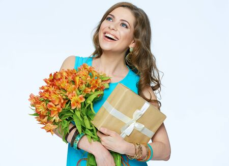 Toothy smiling happy woman holding flower with gift box. White background isolated portrait.