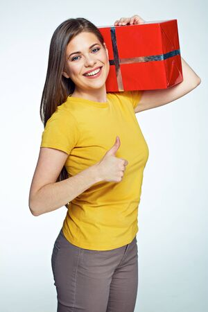 Smiling woman holding big red gift box show thumb up. Long hair. White background. Stock Photo