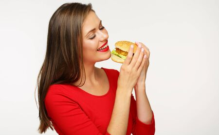 Woman eating burger. Isolated portrait on white back.