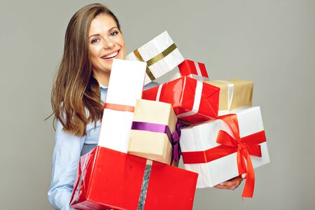Smiling business woman holding pile, stack, heap of presents, gift box. Isolated portrait.