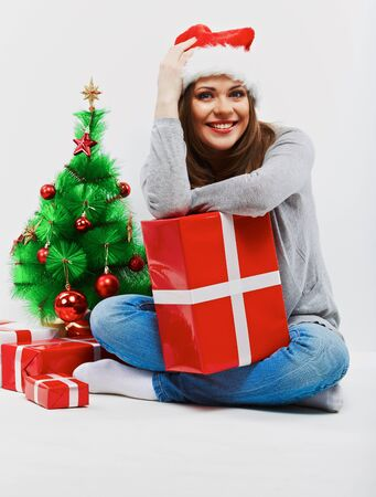 Santa woman seat near Christmas tree with christmas gift. Isolated smiling woman in santa hat.