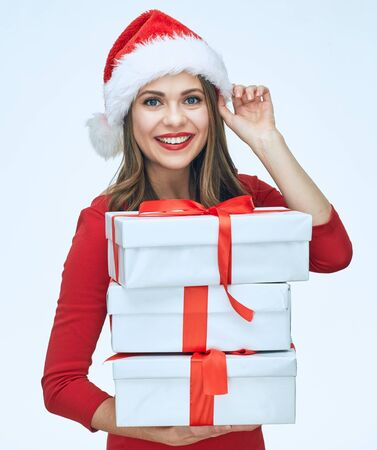 Happy young woman in red christmas dress and Santa hat holding gift box. Isolated portrait.