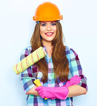 Jonge vrouw met gekruiste armen met verfroller, staande tegen een witte muur als achtergrond. Studioportret van glimlachende vrouw.