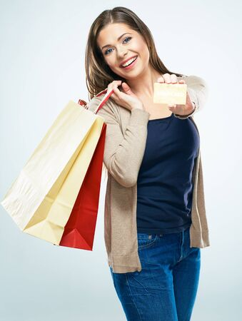 Shopping with credit card. Happy woman hold shopping bag. Studio islated portrait.