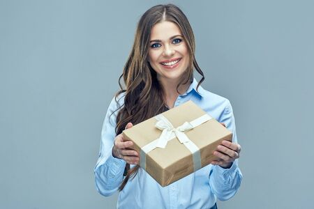 Business woman holding paper gift box. Toothy smiling face. Isolated background.