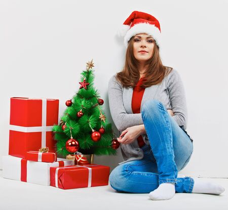 Christmas santa woman with christmas gift. Isolated smiling woman in santa hat.