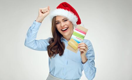 Happy businesswoman wearing Christmas Santa hat holding credit card with passport for successful travel. Isolated portrait.
