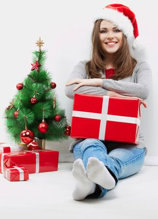 Christmas Santa hat isolated woman portrait hold christmas gift beside green  Christmas Tree. Smiling happy girl seat against white wall. Stock Photo