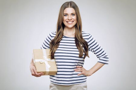 Smiling woman holding gift box. Girl wearing striped sweatshirt isolated portrait.