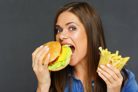 Smiling woman holding french fries with burger, fast food set. Isolated portrait.