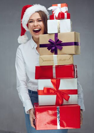 Happy business woman Santa girl holding heap of christmas gift. Isolated portrait.