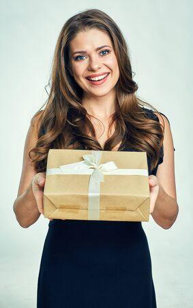 Happy woman holding gift box. Isolated portrait og girl wearing black dress.