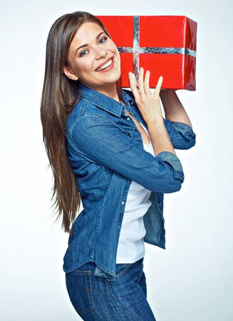 Smling woman hold big gift box. Toothy smiling beautiful model standing against white background with red present. Stock Photo