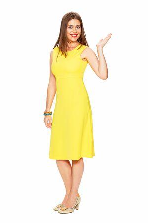 Portrait complet du corps d'une femme souriante en robe jaune pointant du doigt.