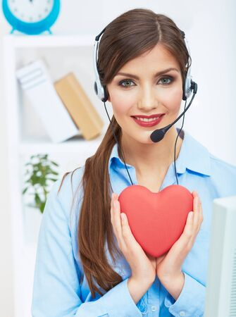 Portrait of call center smiling operator with phone headset isolated on white office background hold red heart. Help concept.
