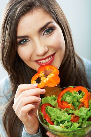 Woman eating green salad . Female model close up face studio isolated portrait .