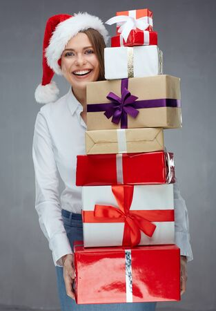 Santa businesswoman holding heap of christmas gifts. Studio portrait.